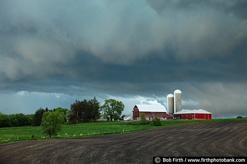 Barns;agriculture;country;farm;farm buildings;rural;spring;spring storm;storm clouds;spring trees;spring farm field;approaching storm;silo;silos;red barn;farm field;farmstead;clouds;midwest farm