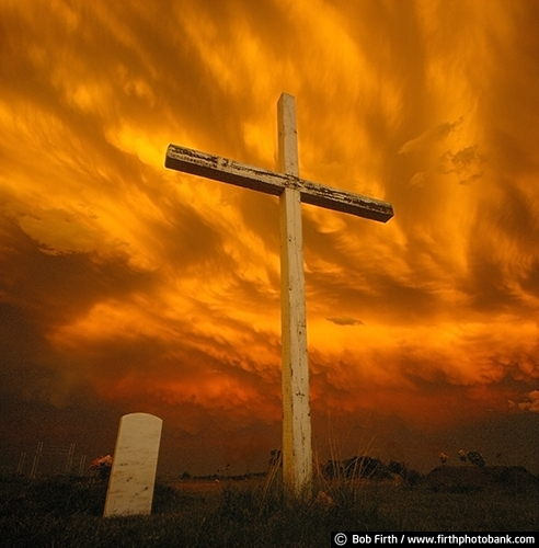 cemetery;cross;country;inspirational;religious;sunset;symbolic;symbolism;storm clouds;South Dakota;SD;powerful;ominous sky;grave marker;grave stone;dramatic light;orange sky